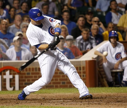 Chicago Cubs' Darwin Barney swings on a three-run home run off Los Angeles Angels starting pitcher Joe Blanton during the sixth inning of a baseball game Tuesday, July 9, 2013, in Chicago. (AP Photo/Charles Rex Arbogast)