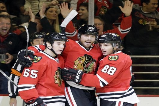 Viktor Stalberg (middle) celebrates with Patrick Kane (88) and Andrew Shaw (65) after his second-period goal (AP)