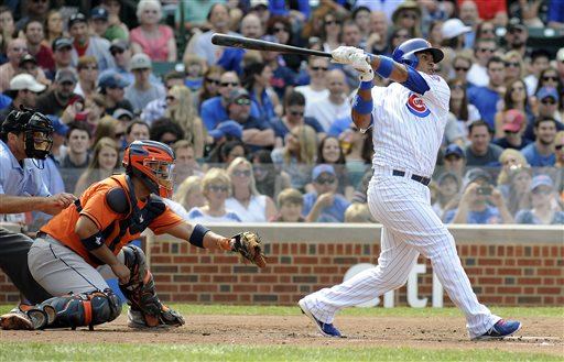 Chicago Cubs' Luis Valbuena, right, hits a two-run single during the third inning of a baseball game against the Houston Astros, Saturday, June 22, 2013, in Chicago, Ill. Astros catcher Carlos Corporan, center, looks on. (AP photo/Joe Raymond)