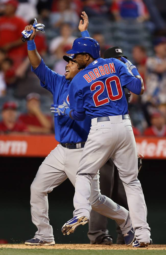 Luis Valbuena (L) #24 and Julio Borbon #20 of the Chicago Cubs celebrate as they score on a hit by Anthony Rizzo (not pictured) against the Los Angeles Angels of Anaheim in the tenth inning at Angel Stadium of Anaheim on June 5, 2013 in Anaheim, California. The Cubs defeated the Angels 8-6 in ten innings. (Photo by Jeff Gross/Getty Images)