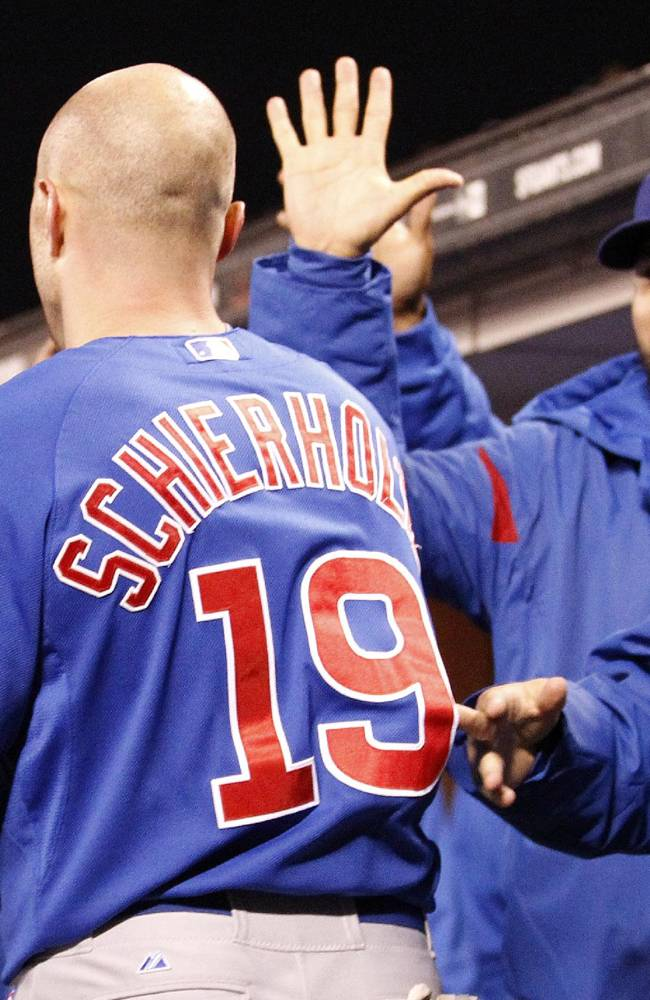Chicago Cubs' Nate Schierholtz, right, is congratulated by teammates after scoring a run on a single Starlin Castro against San Francisco Giants during the sixth inning of a baseball game on Friday, July 26, 2013, in San Francisco. (AP Photo/Tony Avelar)